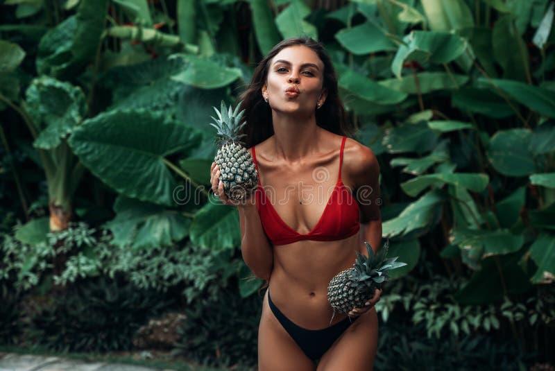 Девушка показывает ей губы поцелуй Красивая модель в купальнике с ананасом в руках представляя против предпосылки  стоковая фотография rf