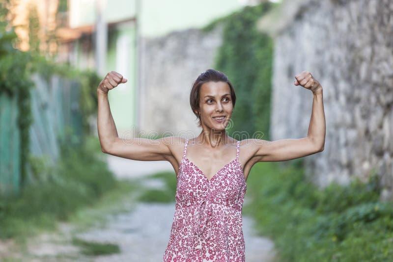 Девушка показывает ей мышцы стоковые изображения rf