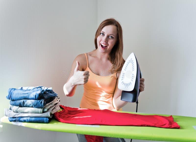 Девушка показывая большие пальцы руки вверх и утюжа одежды утюгом стоковые изображения