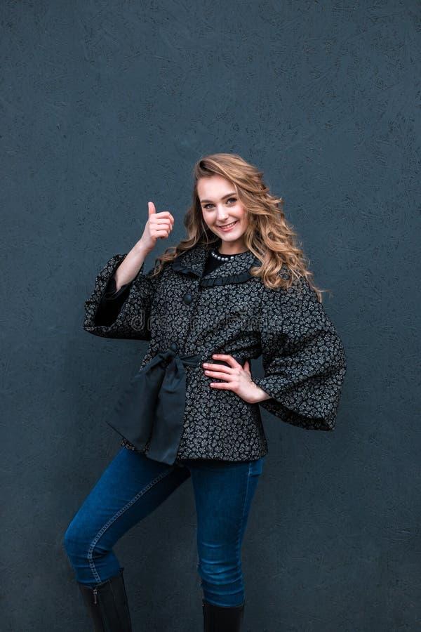 Девушка показывая большие пальцы руки вверх над черной предпосылкой стоковые фото
