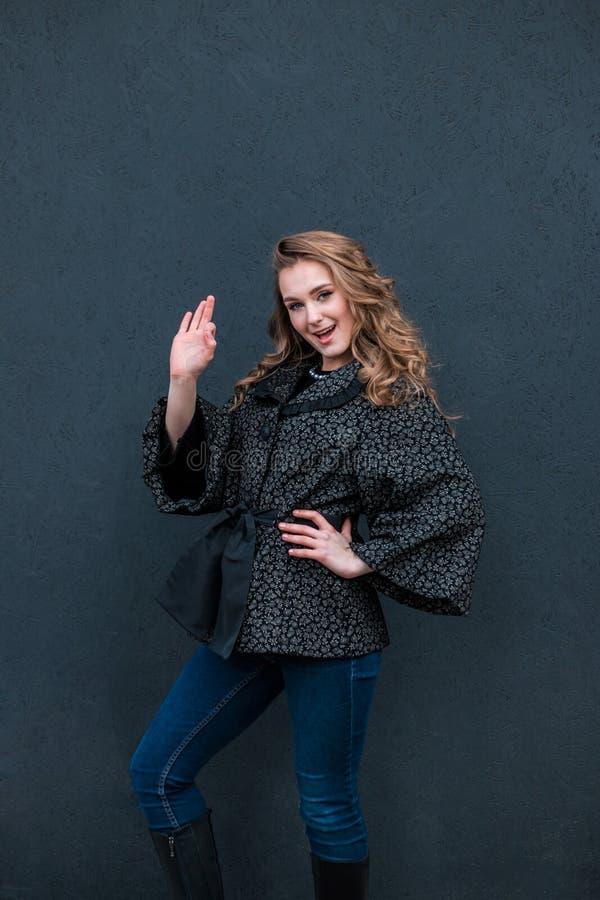 Девушка показывая большие пальцы руки вверх над черной предпосылкой стоковая фотография rf