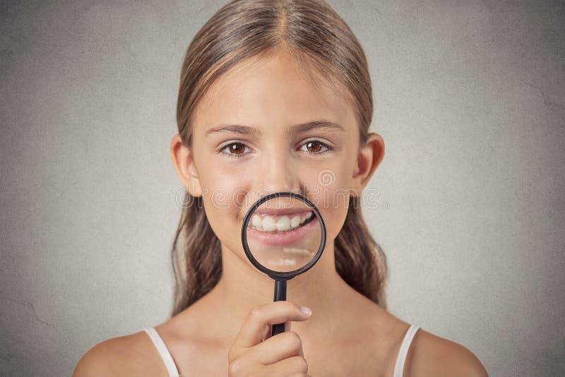 Девушка показывая зубы через лупу стоковые изображения rf
