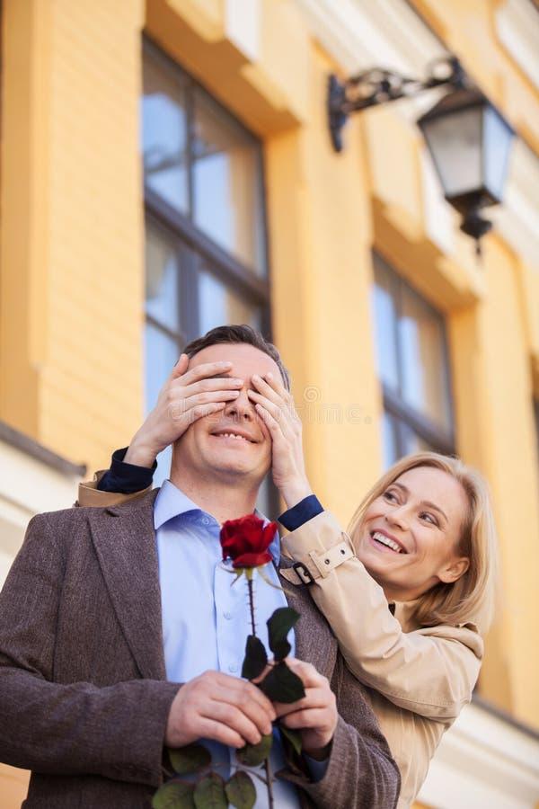 Девушка покрывая глаза ее парня удивила его стоковая фотография