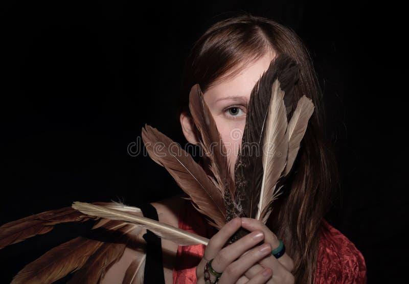 Девушка покрывая сторону с пер стоковые фото