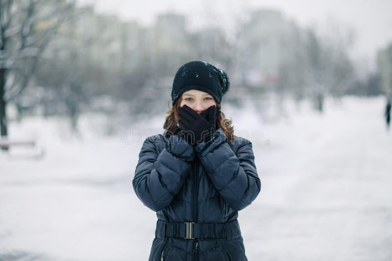 Девушка покрыла рот с перчатками Девушка сделала жест, безмолвие Ребенок идет после школы на улице в снежности стоковая фотография rf