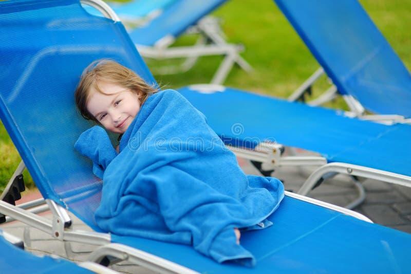 Девушка покрытая при полотенце сидя около бассейна стоковое фото