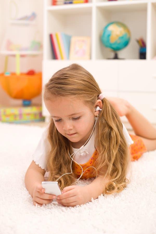 девушка пола кладя слушать меньшее нот к стоковое фото rf