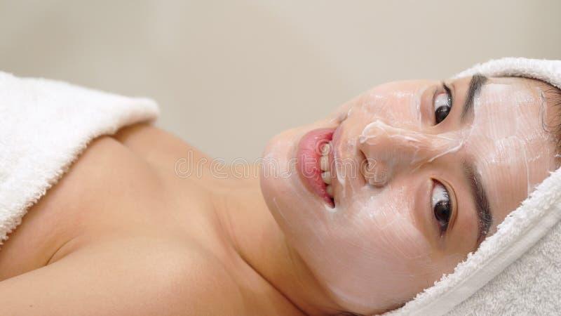 Девушка получает лицевую маску на салоне красоты стоковое фото rf