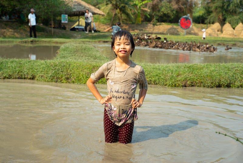 Девушка портрета азиатская влажная наслаждается играми в пруде грязи и гонится группу в составе утки в ферме стоковое фото