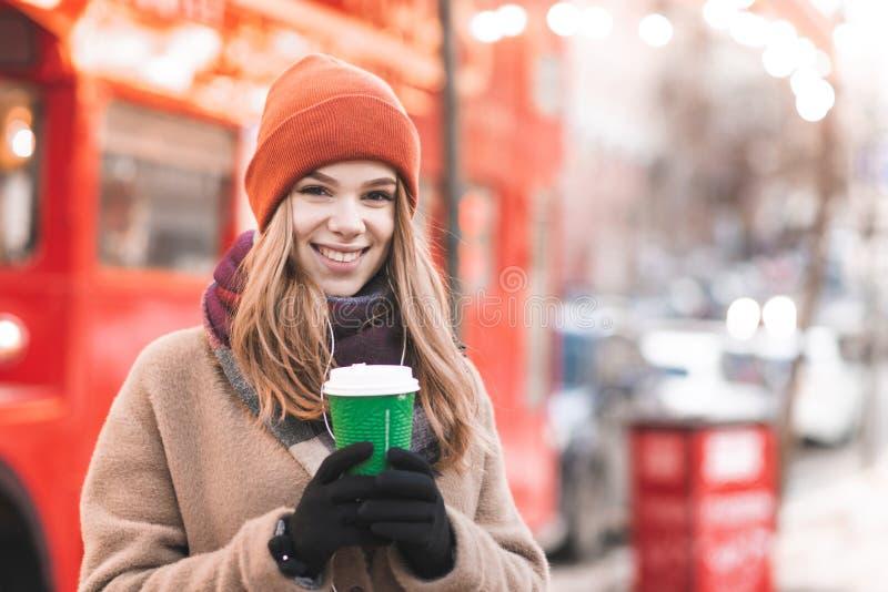 Девушка портрета красивая в теплой одежде стоя в улице с бумажным стаканчиком кофе на bokeh предпосылки, смотря камеру стоковое фото