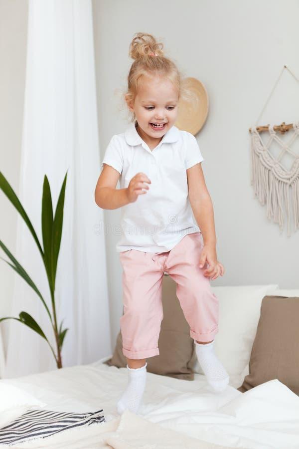 Девушка портрета маленькая милая усмехаясь играя и скача в спальню стоковая фотография rf