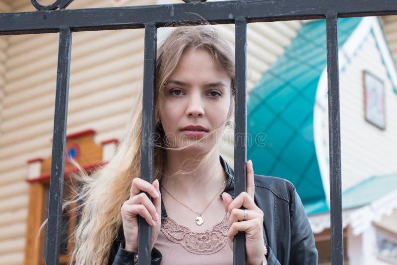 Девушка портрета с светлыми волосами около решетки стоковые изображения