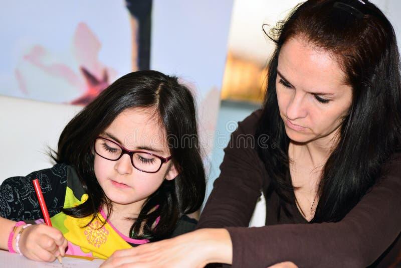 Девушка порции матери для того чтобы сделать домашнюю работу стоковое изображение