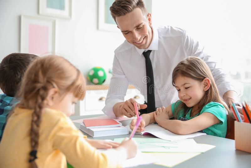 Девушка порции мужского учителя с ее задачей в классе стоковое изображение rf