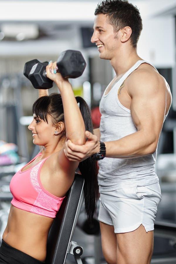 Девушка порции тренера фитнеса в спортзале стоковые фотографии rf