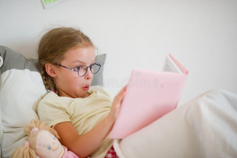 Девушка потехи в стеклах читая книгу пока лежащ в кровати стоковая фотография
