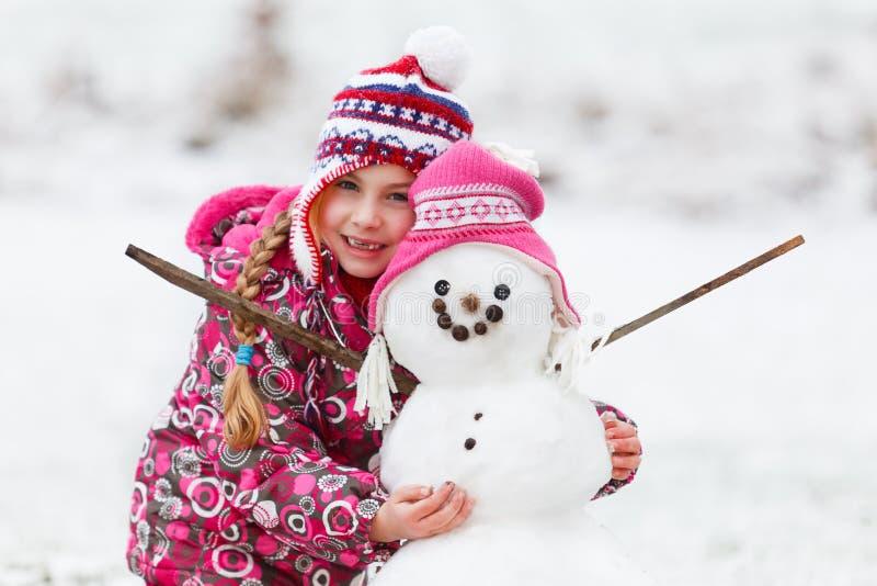 девушка потехи ее зима снеговика стоковое фото rf