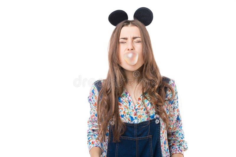 Девушка потехи закрыла ее глаза и жевательная резинка дуновения стоковое фото