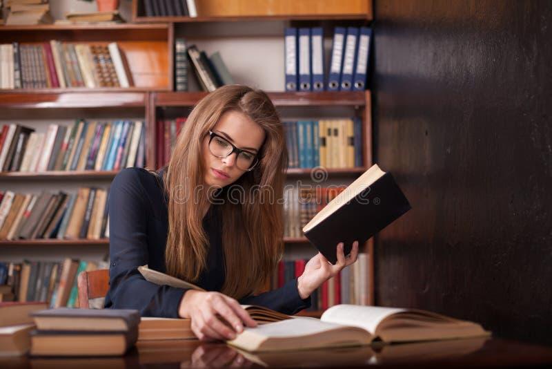 Девушка подготавливает для экзамена читает книги стоковые изображения rf