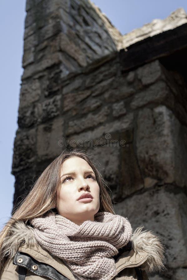 Девушка под каменной стеной стоковые изображения