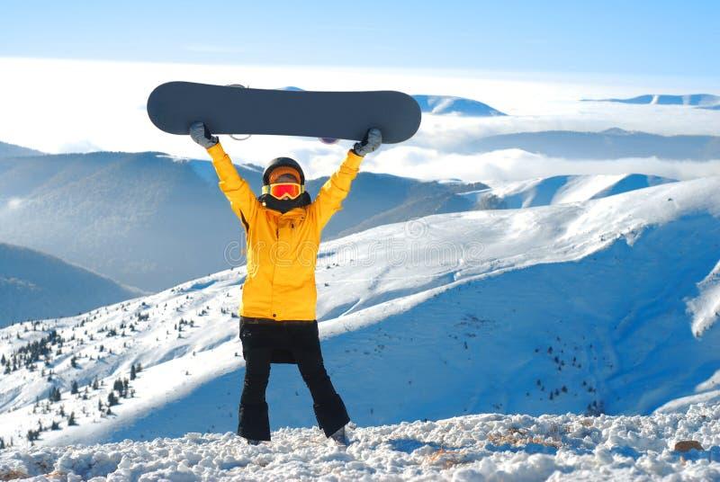 Девушка поднимает сноуборд вверх против панорамной горы зимы стоковое изображение rf