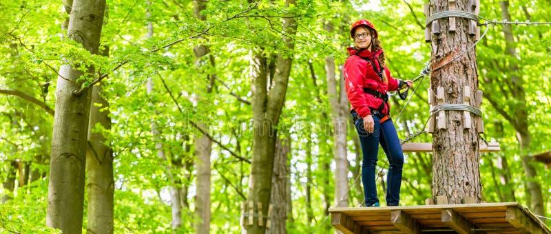 Девушка подростка взбираясь в высоких курсе или parl веревочки стоковая фотография