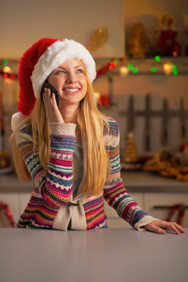 Девушка подростка в сотовом телефоне шляпы santa говоря стоковая фотография