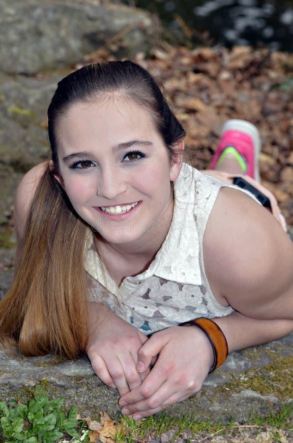 Девушка подростка лежа снаружи стоковое изображение rf