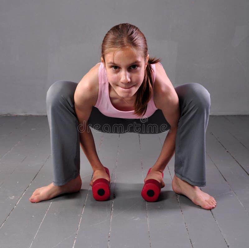 Девушка подростка делая тренировки с гантелями для того чтобы превратиться с гантелями muscles на серой предпосылке Полнометражны стоковые изображения