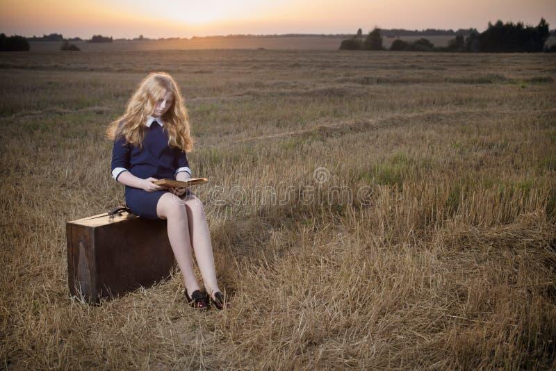Девушка подростка на поле на заходе солнца стоковое фото