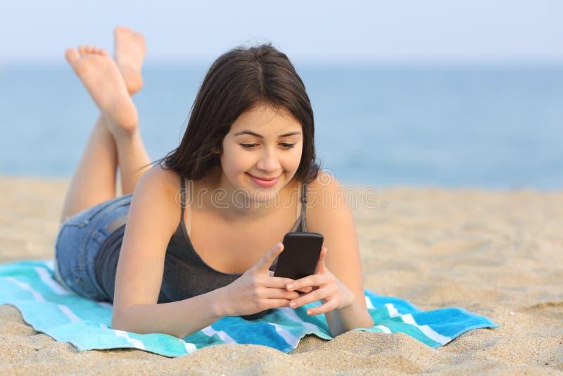 Девушка подростка отправляя СМС умный телефон лежа на пляже стоковая фотография