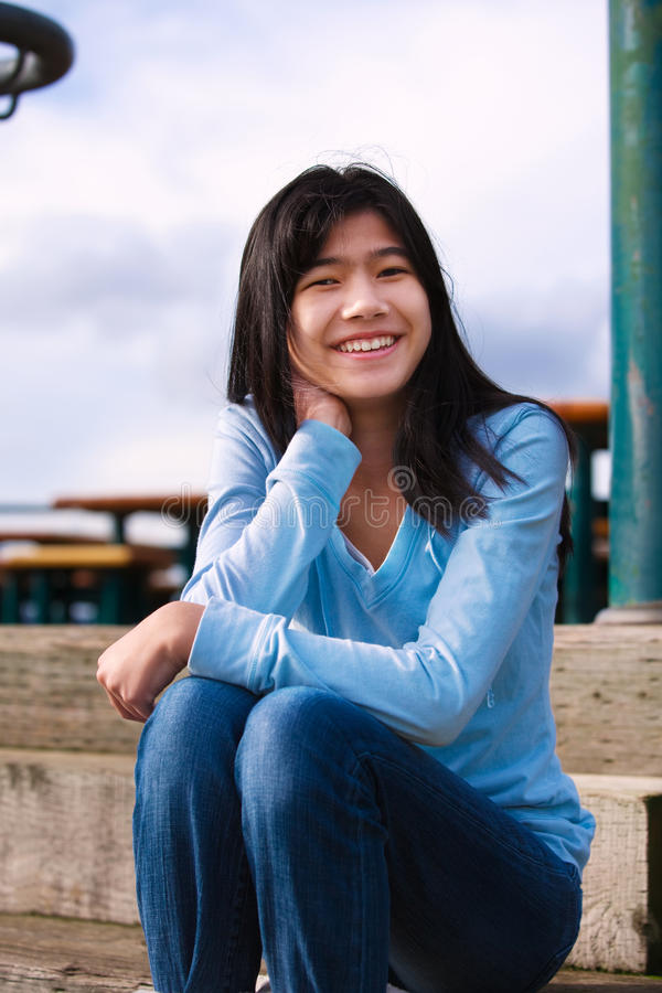 Девушка подростка сидя на деревянных шагах outdoors на день overcast пасмурный стоковое изображение