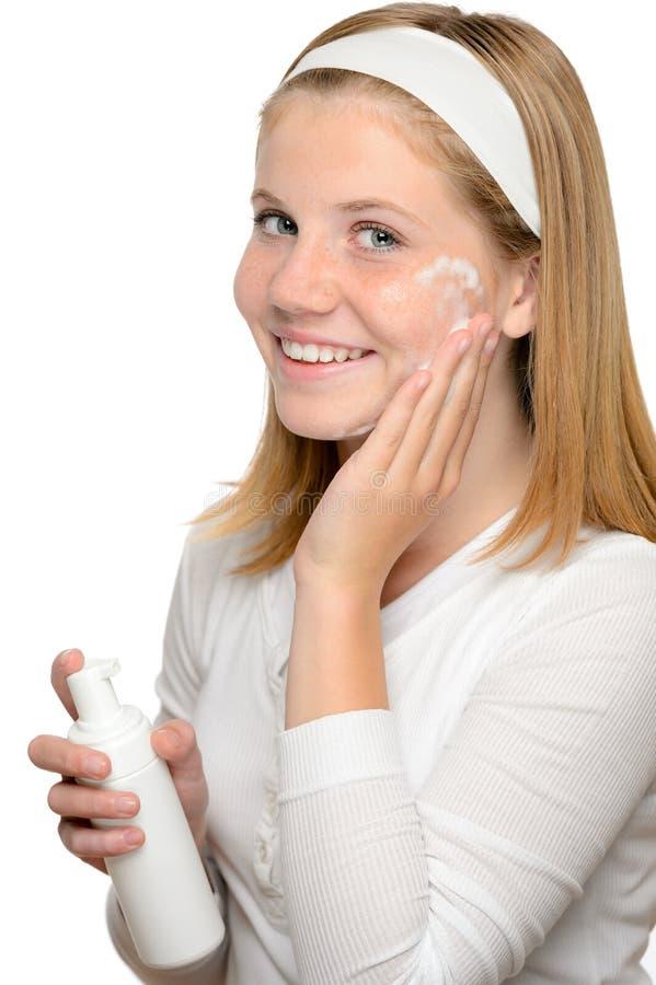 Девушка подростка усмехаясь прикладывающ лосьон увлажнителя  стоковые фото