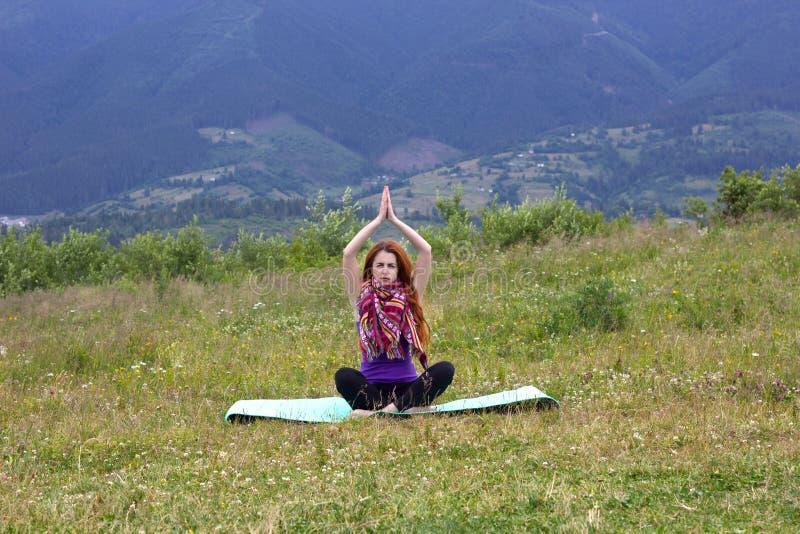 Девушка практикует йогу в горах стоковое фото rf