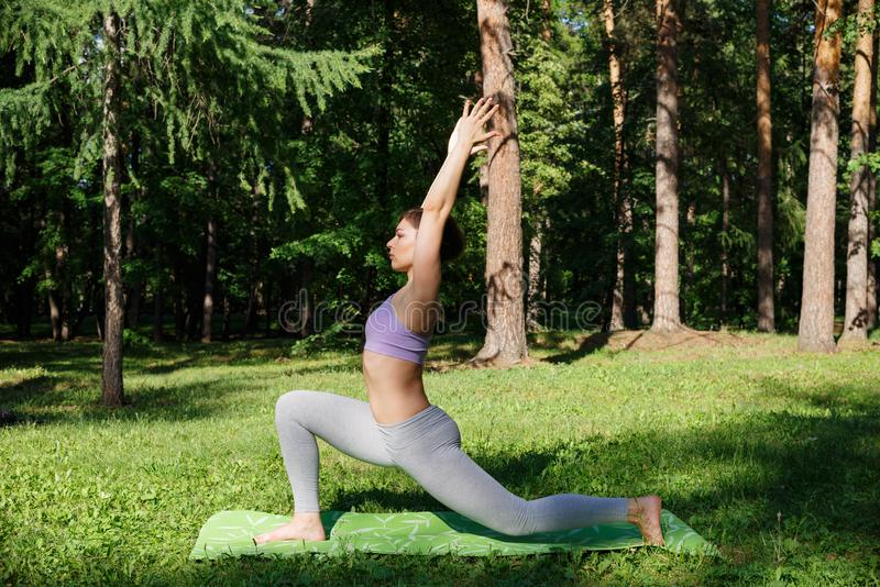 Девушка практикует йогу в парке на солнечный день стоковая фотография rf