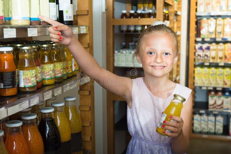 Девушка представляя с бутылкой сока в супермаркете стоковое изображение