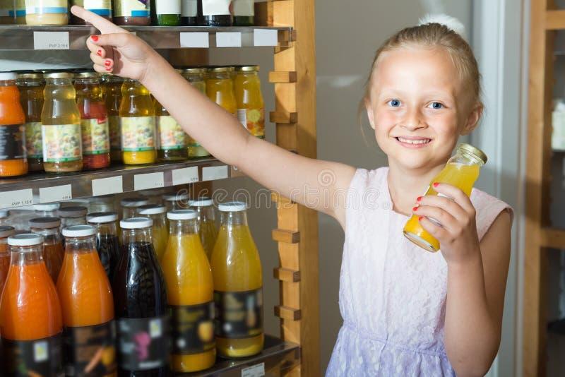 Девушка представляя с бутылкой сока в супермаркете стоковая фотография rf