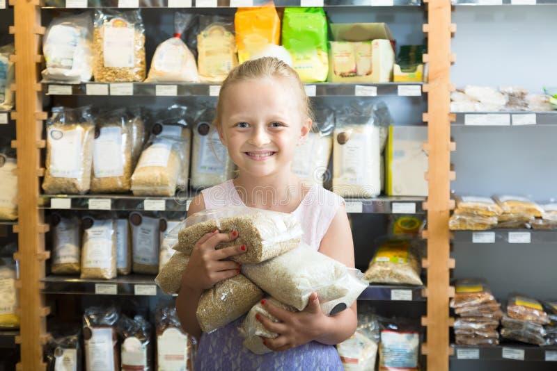 Девушка представляя с пакетами риса в супермаркете стоковые фотографии rf
