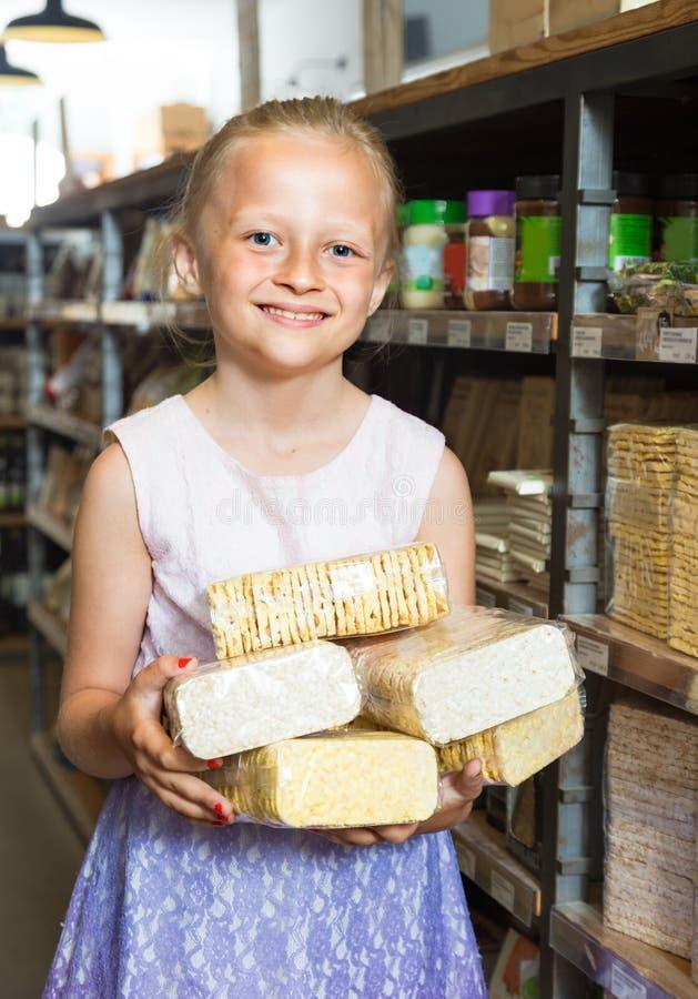 Девушка представляя с печеньями в супермаркете стоковые фото