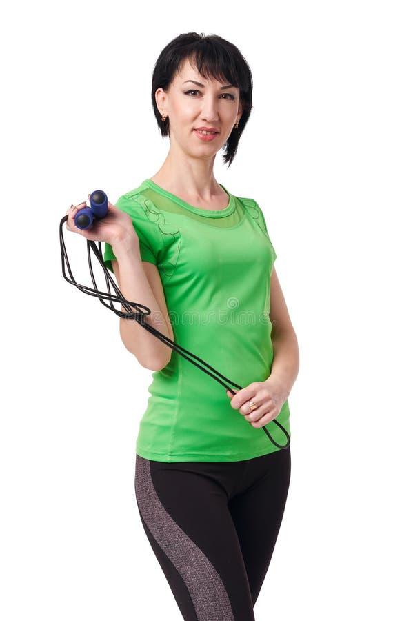 Девушка представляя с прыгая веревочкой в студии, изоляте на белой концепции предпосылки, спорта и здоровья стоковая фотография