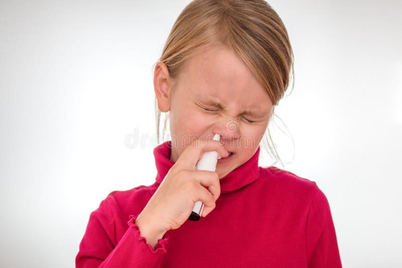 Девушка преодолевает его страх и использует носовой брызг изолированный на белизне стоковые изображения