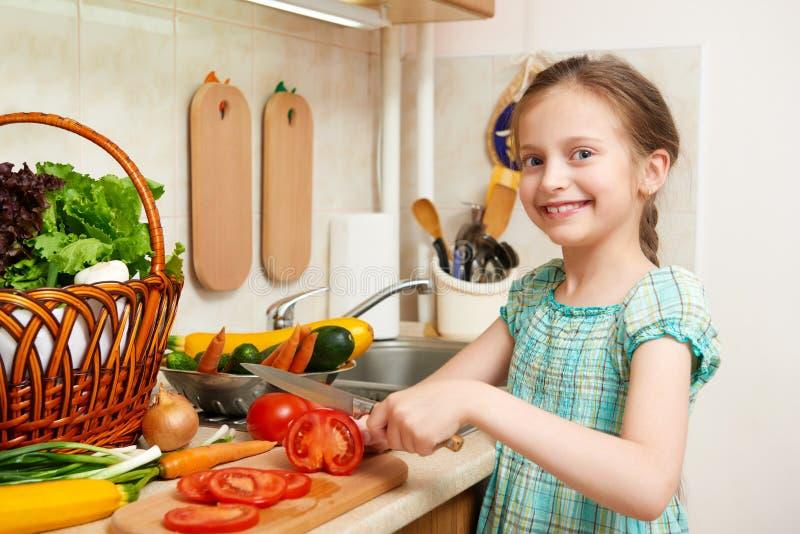 Девушка прерывая томаты, овощи и свежие фрукты в кухне внутренней, здоровой концепции еды стоковые изображения