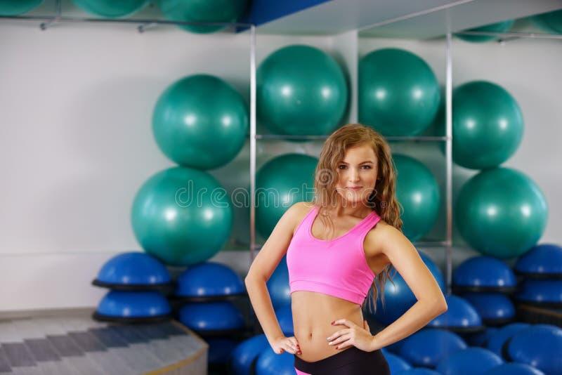 Девушка представляет на фоне стойки с шариками фитнеса стоковые фото