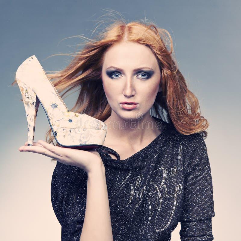 Девушка представляя в студии с ботинком стоковая фотография rf
