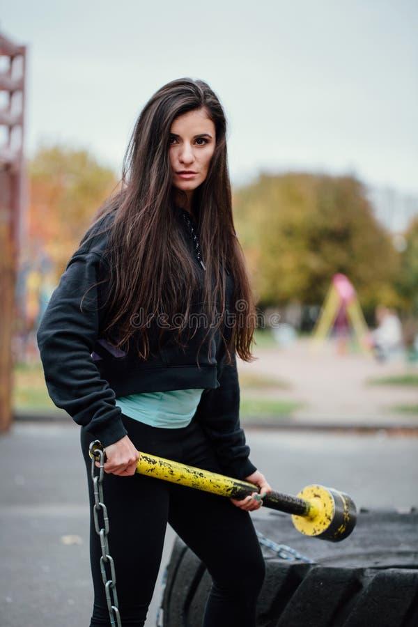 Download Девушка представляя на парке с автошиной молотка и трактора Стоковое Изображение - изображение насчитывающей пригонка, тренировка: 81805351