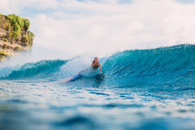 Девушка прибоя на surfboard Wipeout женщины серфера от surfboard на голубой волне стоковое фото