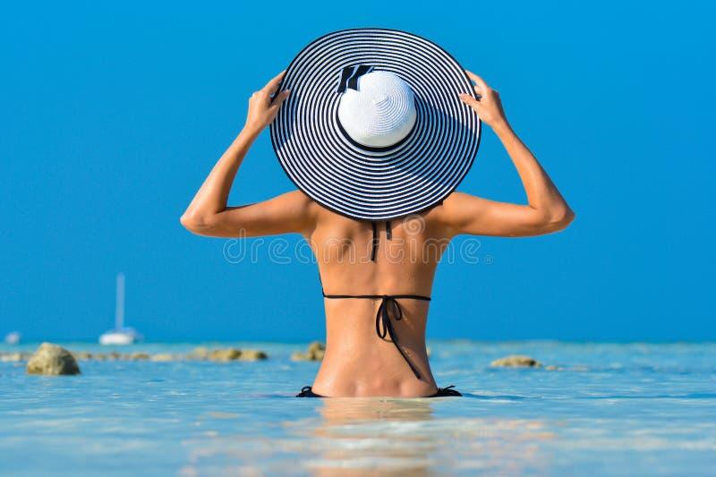 Девушка пригонки на тропическом пляже со шляпой Сексуальная женщина тела бикини на пляже рая тропическом Красивая подходящая деву стоковое изображение