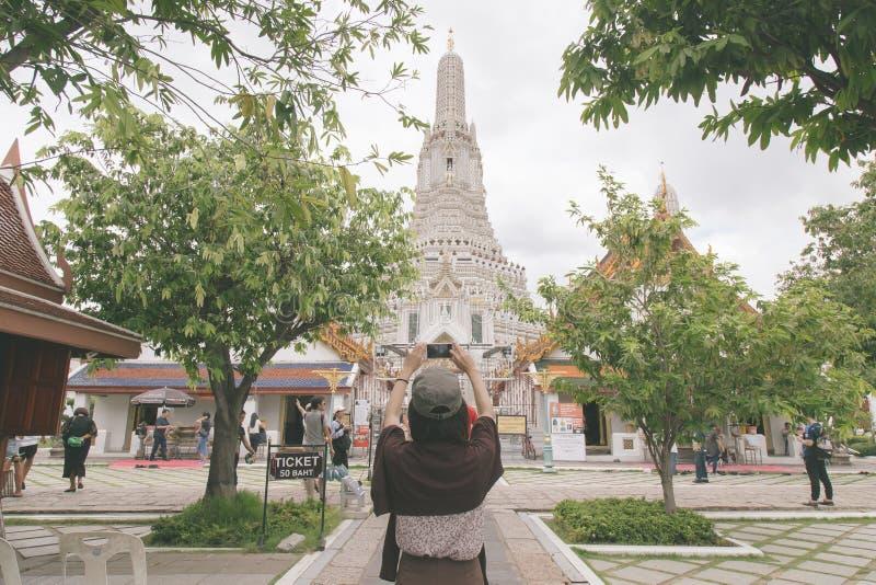 Девушка принимает фото на молитвенном месте для того чтобы помолить для буддизма стоковая фотография