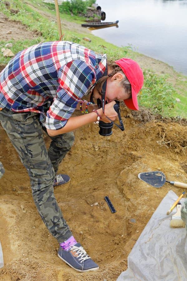 Девушка принимая фото археологических находок во время шариков поля экспедици-старых стоковое фото