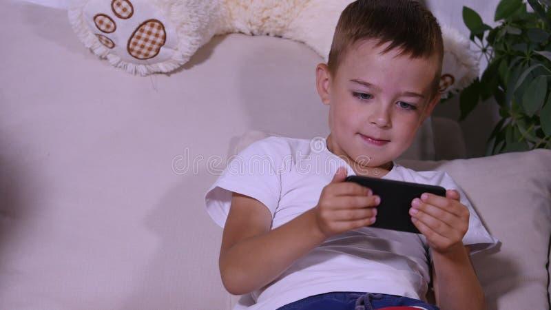 Девушка причаливает мальчику и принимает телефон для того чтобы сыграть стоковая фотография